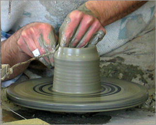 The potter handmades the shape throwing the clay on the wheel